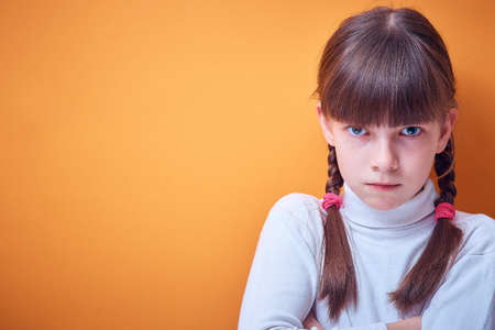angry Caucasian teen girl on colored background, place for text