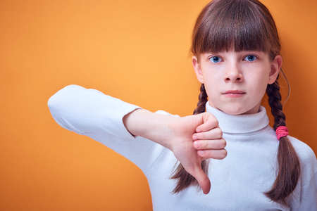 disagreement and protest, Caucasian teen girl shows thumb down on colored background, place for text