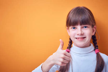 approval and consent, Caucasian teen girl shows thumb up on colored background, place for text