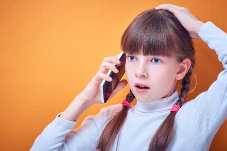 technology and communication, Caucasian teen girl talking on the phone on a colored background, place for text