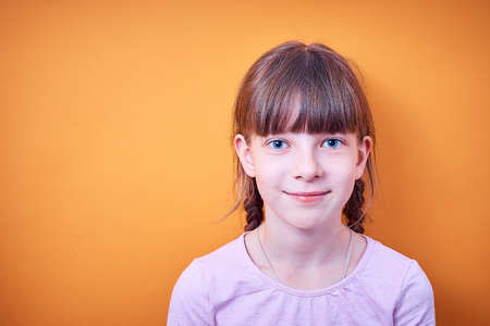 portrait of Caucasian teenage girl with two pigtails on colored background Banco de Imagens