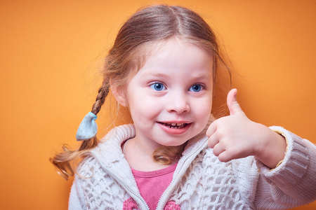 little Caucasian girl approvingly shows thumb up on colored background, place for text Banco de Imagens