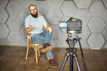 content creation for social media. bearded man shooting video of himself using camera on tripod. modern technology and blogging freelance work concept