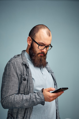 lifestyle brooding man with a beard and a telephone, background, copyspace.