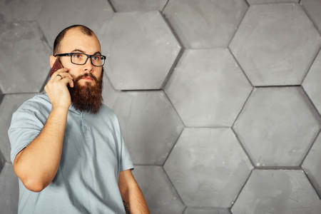 bearded man with glasses talking on a mobile phone Stock Photo