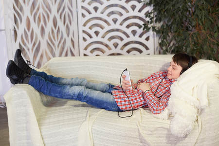 boy listening to music in headphones with phone in hand. Stok Fotoğraf