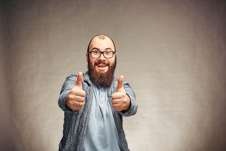he lifestyle of a successful young man with glasses , beard, fashionable denim jacket showing thumbs up,mens emotional portrait in Studio on a plain background Stok Fotoğraf