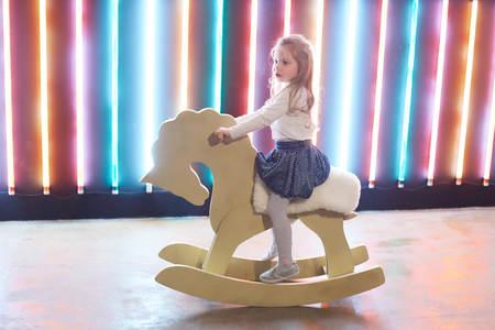 girl riding a horse rocking in an unusual loft Studio. Stok Fotoğraf