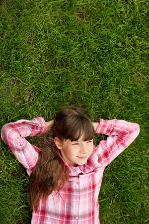 Relaxed teenage girl lying in grass. lifestyle, summer vacation and people concept. Stok Fotoğraf