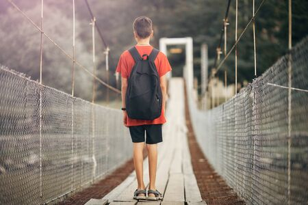 teenager with a backpack in the mountains , a boy crosses a mountain river on a suspension bridge.