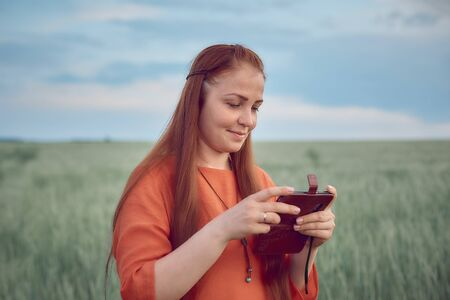 young beautiful woman in red dress with red hair. watch your photos on your phone and stands in a green wheat field in the evening at sunset. modern digital technology. Stok Fotoğraf