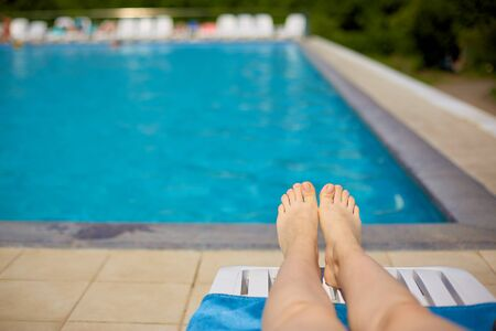 womens legs on the background of the pool with blue water in the open air. Travel, healthy lifestyle