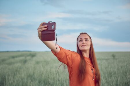 young beautiful woman in red dress and red hair, takes a selfie on the phone in the green wheat field in the evening at sunset in summer. the nature of digital technology.