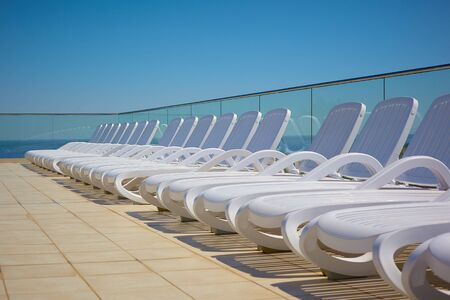 white sun loungers by the pool under the open blue sky. summer holiday. journey. rest by the sea. Stok Fotoğraf
