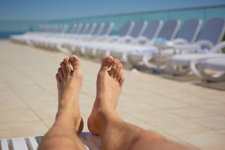 mens legs on the background of sun loungers by the pool. Travel, healthy lifestyle Stok Fotoğraf