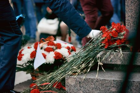 laying flowers at the monument, a soldier in white gloves puts flowers at the monument to soldiers who died in world war II