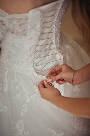 bridesmaids help lace up the corset on the brides dress