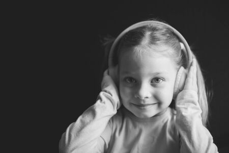 little girl in headphones listening to music, black and white portrait of a Caucasian child