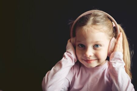 little girl in headphones listening to music, portrait of a Caucasian child