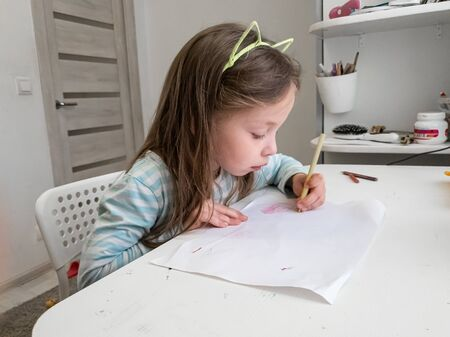 a little girl draws with colored pencils with her left hand, childrens joint creativity