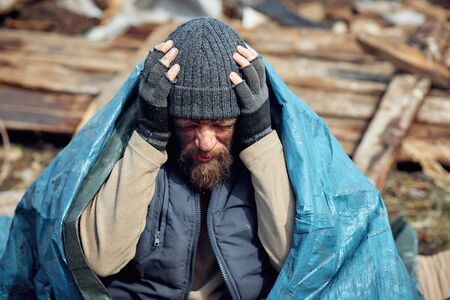 sad and upset homeless and unemployed man in the ruins