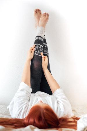 a woman puts on warm gray woolen leggings, women's legs in winter leggings.