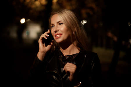 beautiful blonde woman talking on the phone in the evening in the Park, communication and communication