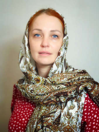 portrait of a red-haired blue-eyed woman in a headscarf, mobile lifestyle photo 写真素材