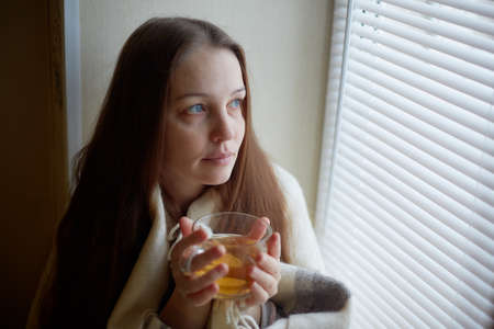 sick beautiful woman with colds and drinks hot tea with lemon sitting by the window in a country house in winter.