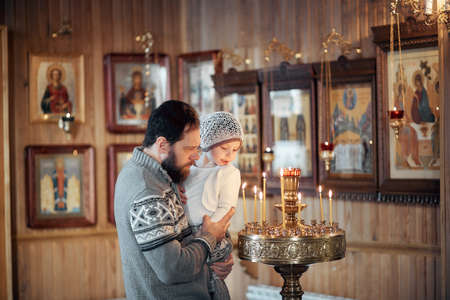 A Russian man with a beard and a daughter is standing in an Orthodox Church, lighting a candle and praying in front of the icon.