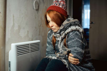 a woman is warming herself at the radiator in a cold house, problems with heating, heating the room with an electric convector