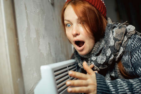 emotional woman warms up at the radiator in a cold house, problems with heating, heating the room with an electric convector