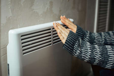 a woman warms her hands at the radiator in a cold house, problems with heating, heating the room with an electric convector