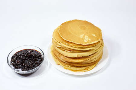 a stack of Russian pancakes and a bowl of cherry jam on a white background, pancakes on Shrovetide before Lent 写真素材