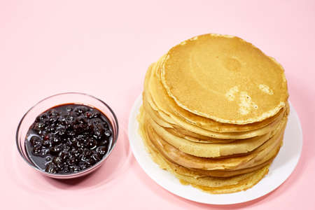 a stack of Russian pancakes and a bowl of cherry jam on a pink background, pancakes for Shrovetide before Lent 写真素材