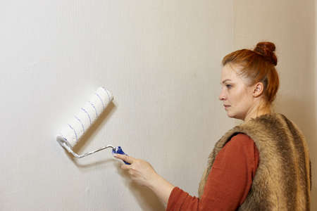 a woman paints the walls of an apartment with white paint, self-repair of the interior 写真素材
