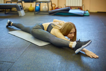 the girl is engaged in stretching and yoga in the gym after training and Pilates, a class in a sports club after quarantine 写真素材
