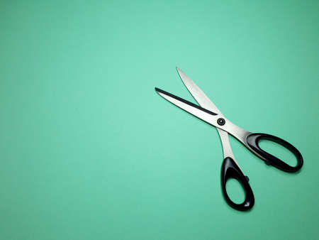 tailor scissors for cutting fabric on a green background