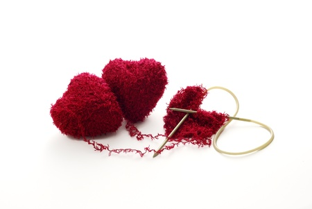 linked together: One heart knitted from two red heart shaped clews Stock Photo