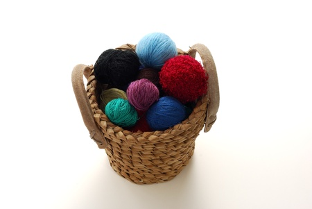 Colorful clews of knitting threads in interwoven basket on white background