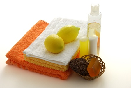 Lemon flavored SPA set including colored towels, soap, shampoo, moisturizer and pumice  on white background