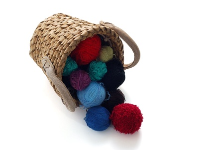 Colorful knitting clews spilled out from interwoven basket