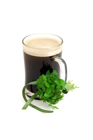 false shamrock: Dark beer in glass and bouquet of false shamrock (Oxalis) with green ribbon on white background