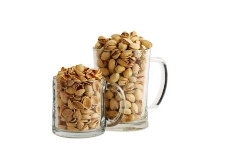 nutshells: Two glass beer mugs filled with salted pistachios and nutshells