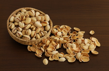 nutshells: Pistachios in interwoven bowl with spilled nutshells on dark wooden table