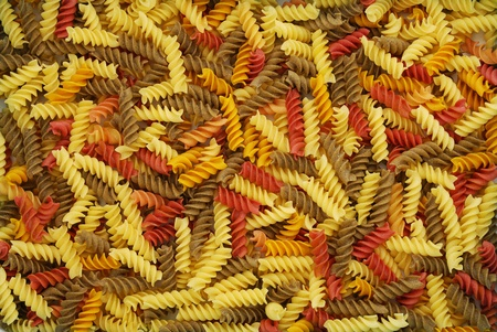 Multicolored dry fusilli pasta background