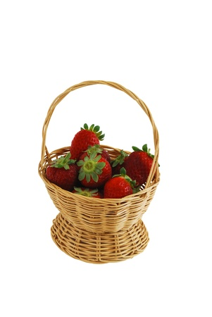 Fresh strawberries in small interwoven straw basket isolated on white background