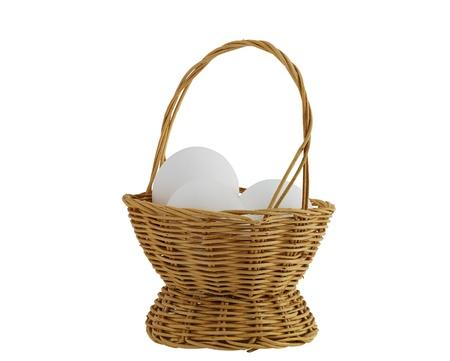 three white eggs in straw interwoven basket isolated on white background Stock Photo