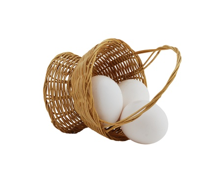 three white eggs spilled from straw interwoven basket isolated on white background