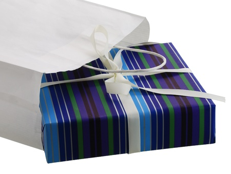 Present wrapped in striped blue paper sticking out from white carry bag isolated on white background  photo